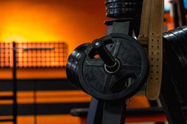 역도 용 가죽 벨트는 체육관에서 10kg의 범퍼 디스크 용 랙에 달려 있습니다.