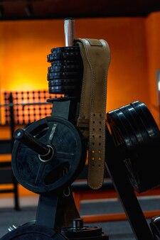 역도 용 가죽 벨트는 체육관의 범퍼 디스크가있는 선반에 달려 있습니다.