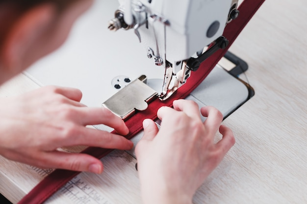 Ремесленник из кожи производит изделия из кожи на швейной машине в своей мастерской.