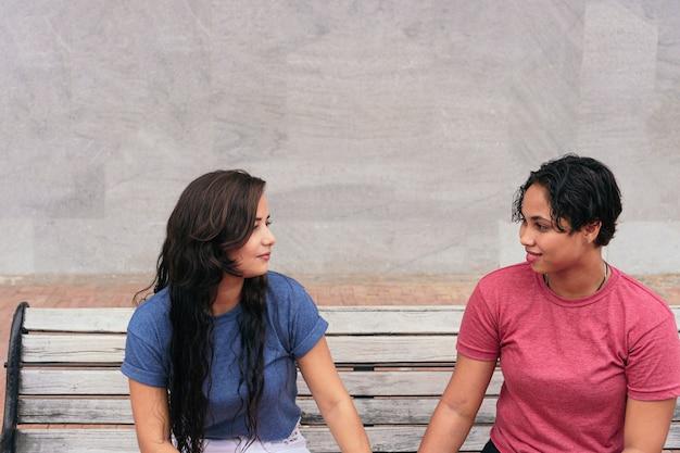お互いの会社を楽しみながら公園のベンチで話しているレズビアンのカップル。