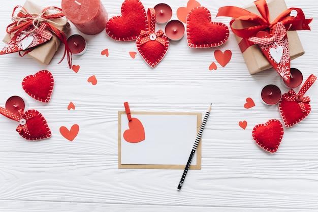Письмо любви, декоративные сердца и подарки на белом деревянном фоне для валентина