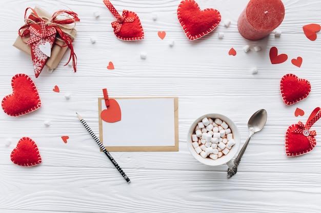 Письмо любви, декоративные сердца, подарки и чашка кофе на белом столе