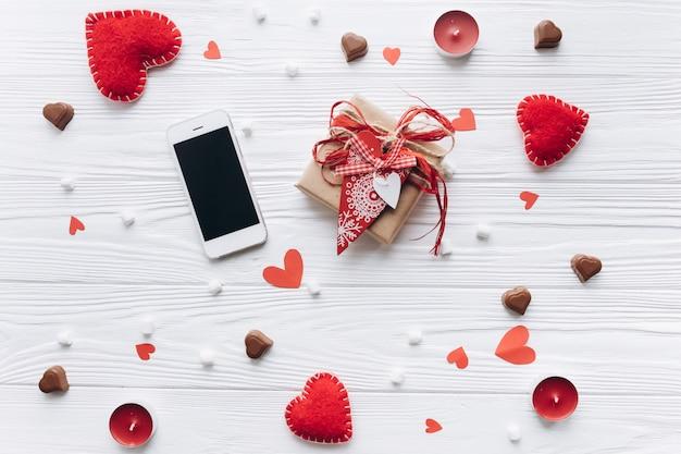 Письмо любви, декоративные сердца, подарки и смартфон на темном белом столе