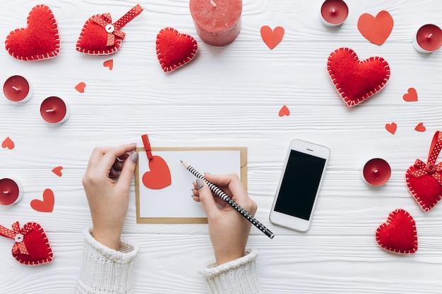 Письмо любви, декоративные сердца, подарки и смартфон на белом столе для валентина