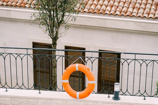 救命浮環は、プールの近くのシャッター付きの家の外にある金属柵のロープからぶら下がっています。