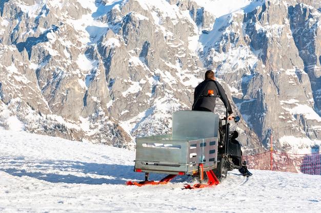 Спасатель едет на снегоходе с санями по горнолыжному склону