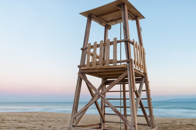 Вышка спасателей на средиземноморском пляже на закате летом