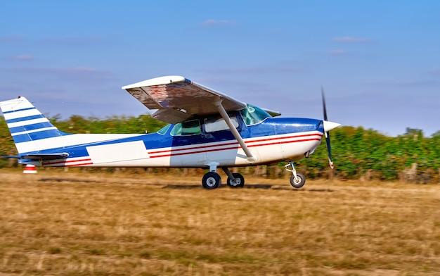 軽飛行機がブドウ園近くの畑で離陸します。晴れた夏の日、人々は見守り、植えます。