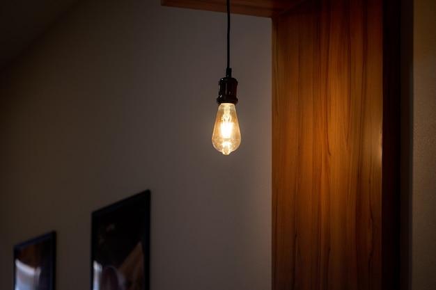 天井からぶら下がっている電球が少し暗い部屋を照らしています。部屋の装飾のアイデア。