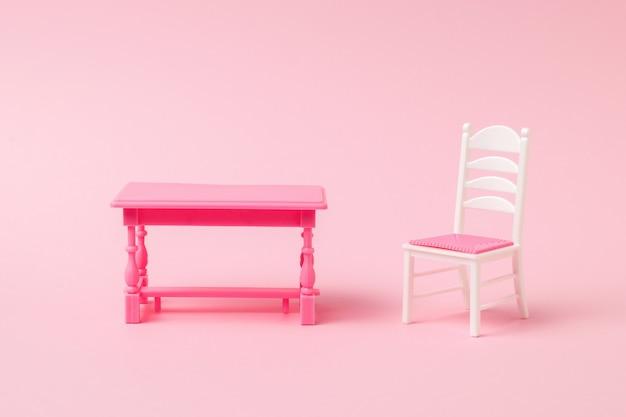淡いピンクの表面に軽い椅子と赤いテーブル