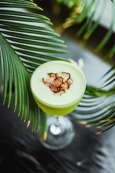 Светло-зеленый коктейль из кислой текилы в бокале nick and nora, гарнир из чипсов из редьки, среди пальмовых листьев