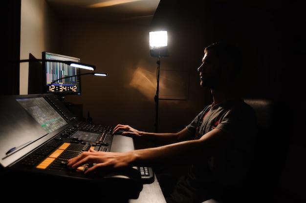 照明技術者は、コンサートショーの照明技術者が操作します。プロフェッショナルライトミキサー、ミキシングコンソール。コンサートのための機器。