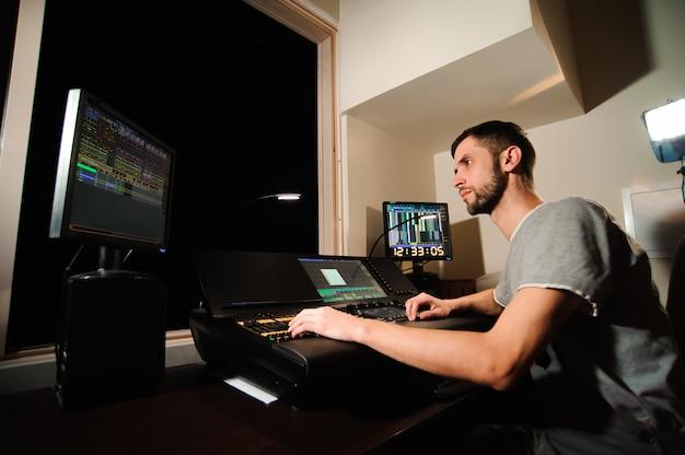 조명 엔지니어는 콘서트 쇼에서 조명 기술자 컨트롤과 함께 작업합니다. 전문 조명 믹서, 믹싱 콘솔. 콘서트 장비
