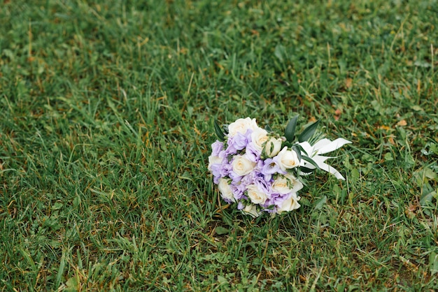 라일락과 베이지 색 웨딩 부케는 푸른 잔디에 놓여 있습니다.