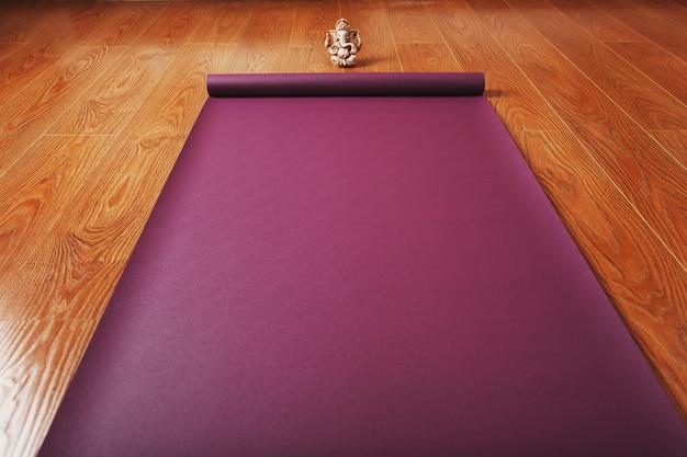 На деревянном полу расстелен коврик для йоги сиреневого цвета с фигуркой ганапати. вид сверху