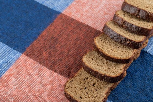 Линия ломтиков черного хлеба на скатерти.
