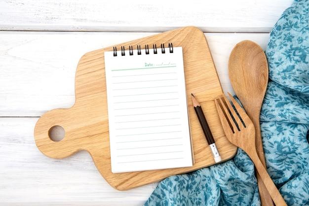 木製のフォークとカッティングボードとテーブルクロスを切り刻んで並べ替えられた本のメモ帳の紙と
