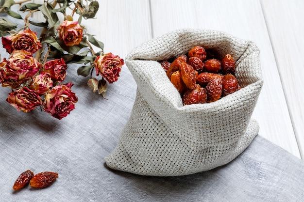 Льняная сумка с сушеными плодами шиповника и веточкой маленьких роз на светлом деревянном столе. понятие народной медицины, лечение натуральными лекарственными растениями.