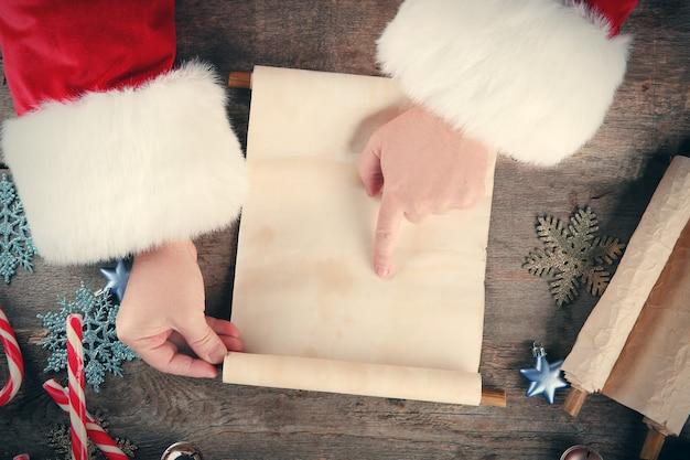 나무 테이블에 산타 클로스 손에 크리스마스 소원 목록