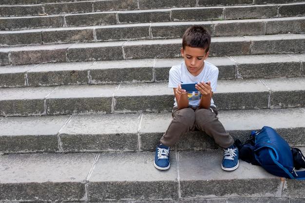 Маленький мальчик сидит с рюкзаком на лестнице с мобильным телефоном