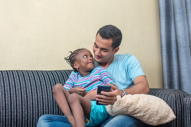 ソファと膝の上に座っている小さなアフリカの女の子または娘彼女の白人の父親