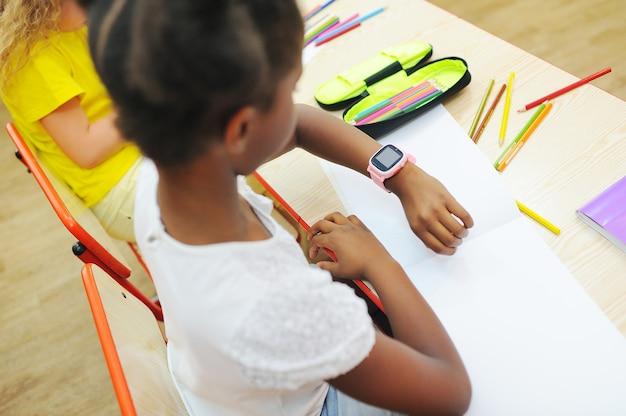 Маленькая афроамериканская девочка, сидящая за партой в начальной школе, смотрит на умные часы на своем ха ...