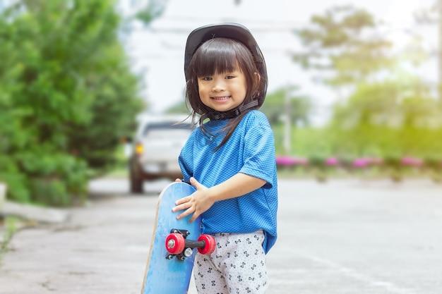 小さなアジアの子供の女の子が遊んでスケートボードに乗っている彼女は公園で安全ヘルメットをかぶっています
