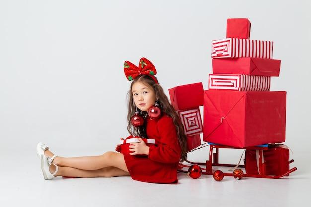 빨간 드레스에 앉아 아시아 소녀 흰색 배경에 선물 상자와 함께 앉는 다. 크리스마스 컨셉, 텍스트 공간