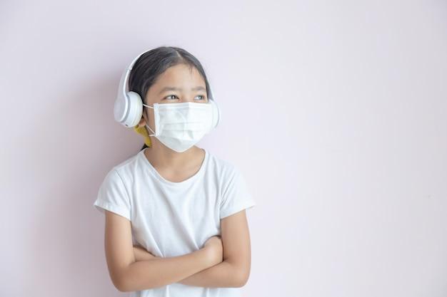 医療用防護マスクとイヤホンを身に着けている小さなアジアの女の子