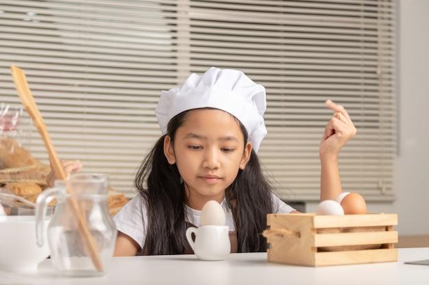 白いシェフの帽子をかぶった小さなアジアの女の子が小さな水差しでアヒルの卵を見つめています