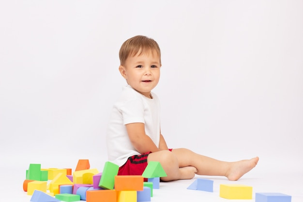 흰색 배경에 격리된 큐브를 가지고 노는 바닥에 앉아 있는 어린 소년.