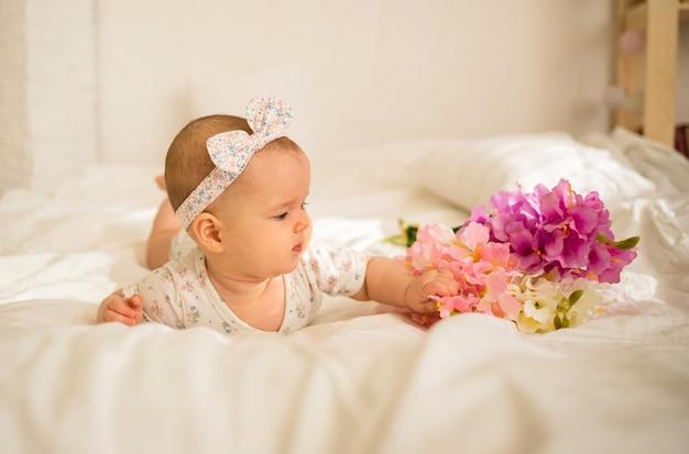 Маленькая девочка в боди лежит на кровати и смотрит на букет цветов