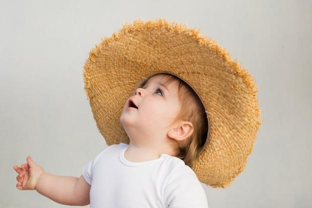 麦わら帽子と白いボディースーツを着た小さな女の赤ちゃんは、テキスト用のスペースで白い意志を見上げます