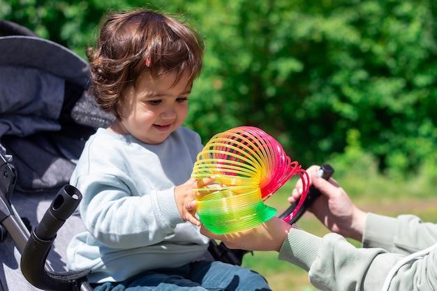 어린 소녀가 운동 능력을 발달시키는 탄력 있는 무지개 장난감을 가지고 놀고 있습니다