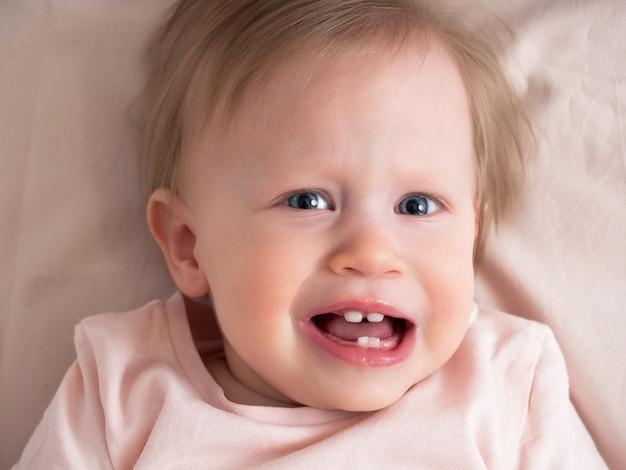 어린 소녀는 고통, 젖니, 카메라 보고, 울고, 클로즈업으로 고통 받고 있습니다. 핑크 톤의 아름다운 빛 소녀의 초상화. 어린이 나이 한 살.