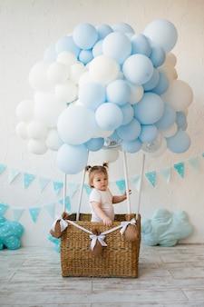 小さな女の赤ちゃんは白い部屋に風船とバスケットに立っています