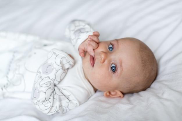 Маленький ребенок лежит на кровати на белой простыне и смотрит