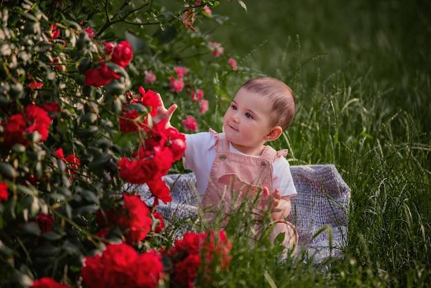 赤いバラの横にある緑の芝生に小さな赤ちゃんが座っています。粉っぽいオーバーオールを着た幸せな女の子が公園を散歩しています。子供のクローズアップの肖像画。のんきな子供時代