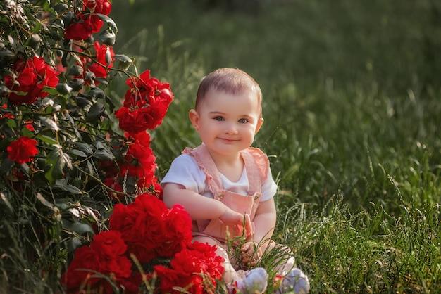작은 아기는 빨간 장미 옆에 녹색 잔디밭에 앉는다. 가루 작업복을 입은 행복한 소녀가 공원에서 산책을 즐깁니다. 아이의 근접 촬영 초상화입니다. 평온한 어린 시절