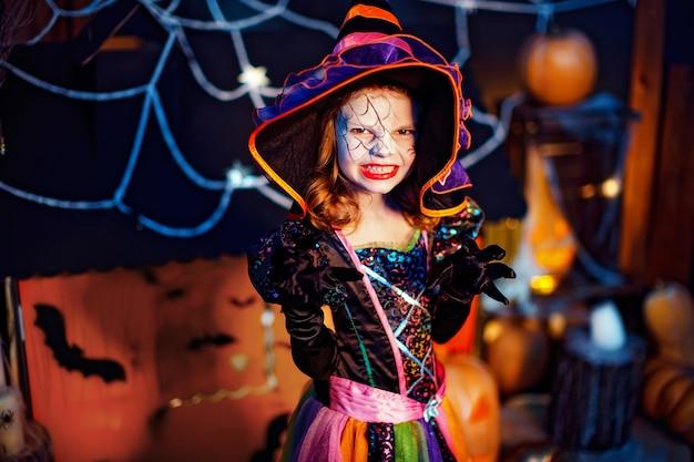 Маленькая красивая девочка в костюме ведьмы празднует дома в интерьере с тыквами и картонным волшебным домом на заднем плане. пугает в камеру.