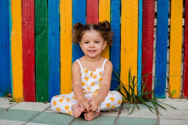 マルチカラーの木製のフェンスの近くに座っている美しい少女