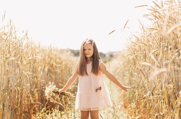 Маленькая красивая девочка с букетом ромашек на пшеничном поле