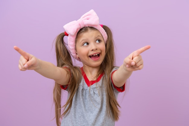그녀의 머리에 분홍색 활을 가진 작은 아름다운 소녀가 미소를 지으며 손가락을 옆으로 가리 킵니다.