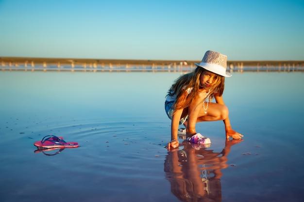 아름다운 흐르는 머리카락을 가진 작은 아름다운 소녀는 투명한 표면에 투명한 물 유약으로 무언가를 본다.