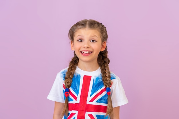 Маленькая красивая девочка с косичками в футболке с изображением английского флага улыбается.