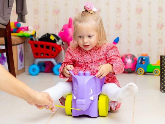 작은 금발 소녀는 놀면서 장난감 차를 탄다