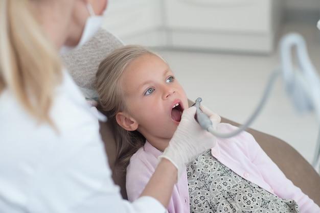 歯科医で歯の治療を受けている小さな金髪の子供