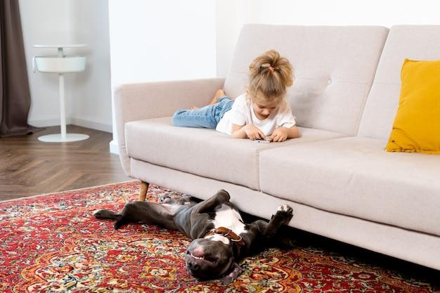 携帯電話と大きな犬、子供とガジェットを持ってソファで家にいる小さなブロンドの女の子。