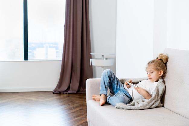 携帯電話、子供、ガジェットを持ってソファに座っている小さなブロンドの女の子。