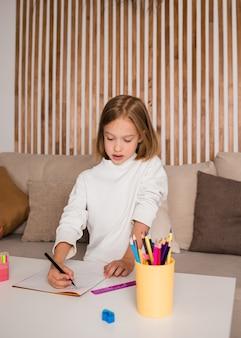 작은 금발 소녀는 종이에 연필로 그립니다. 어린이를 위한 미술
